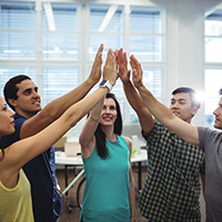 Group of happy business executives giving high five in office
