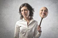 Érzelmi intelligencia tréning - gondterhelt nő mosolygó álarccal